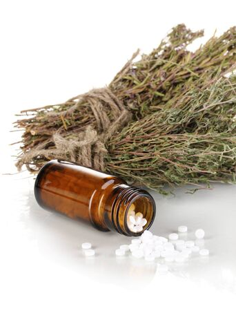cures: bottle of medicines with herbs on white background. concept of homeopathy