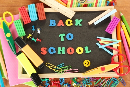Small chalkboard with school supplies on wooden background. Back to School Stock Photo - 16343064
