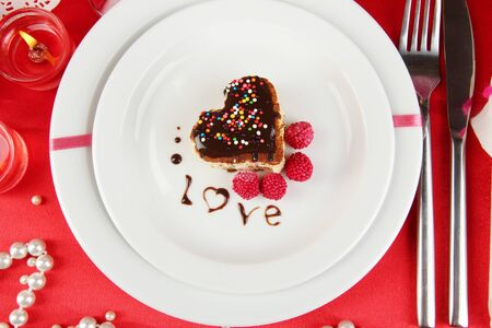 Plate with dessert in form of heart on celebratory table in honor of Valentines Day close-up photo