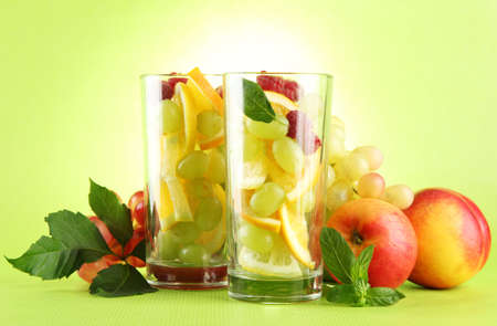 transparent glasses with citrus fruits, on grren background Stock Photo - 16342693