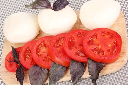 tasty mozzarella with tomatoes on chopping board close-up photo