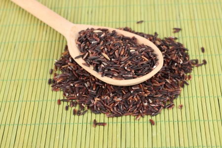 black rice  in wooden  spoon on bamboo mat photo