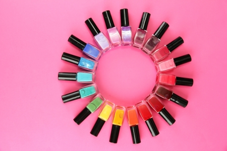 Group of bright nail polishes, on pink background photo