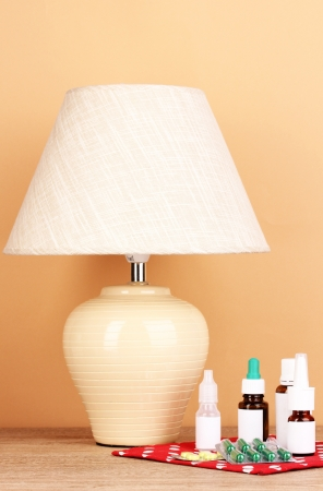 table lamp and medicines on beige background photo