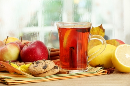 mulled wine: cup of hot tea and autumn leaves, on wooden table