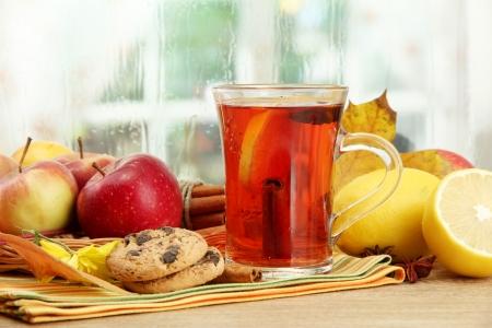 apple cinnamon: tazza di t� caldo e foglie di autunno, su tavola di legno