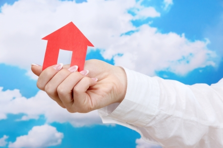 concept: woman hand with paper house on sky background, close up Stock Photo - 16342754