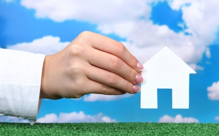 concept: woman hand with paper house on sky background, close up photo