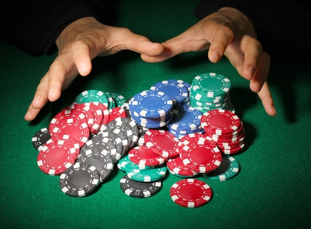 Poker chips and hands above it on green table photo