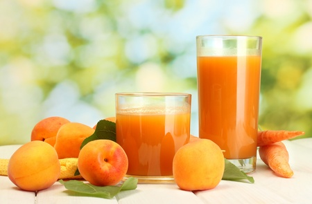 glasses of carrot and  apricot juice on white wooden table on green background photo