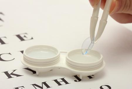 lentes de contacto: lentes de contacto en los contenedores y pinzas, en el fondo snellen tabla optométrica