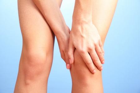 dolor de rodilla: mujer con dolor en la rodilla, sobre fondo azul