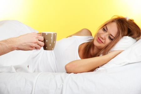 morning coffee in bed for young  woman on yellow background Stock Photo - 17129757