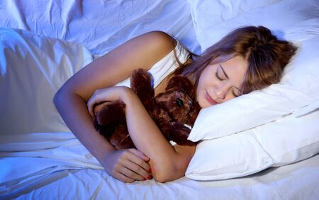 young beautiful woman with toy bear sleeping on bed in bedroom photo