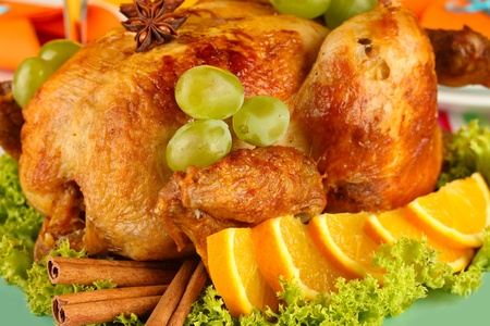 roastes chicken with grapes, lettuce and spices close-up. Thanksgiving Day photo