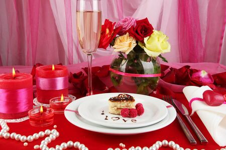Table setting in honor of Valentines Day on white fabric background photo