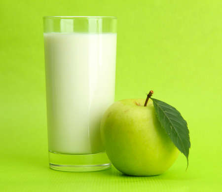 Glass of kefir and apple, on green background photo