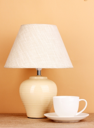 table lamp and cup on beige background photo