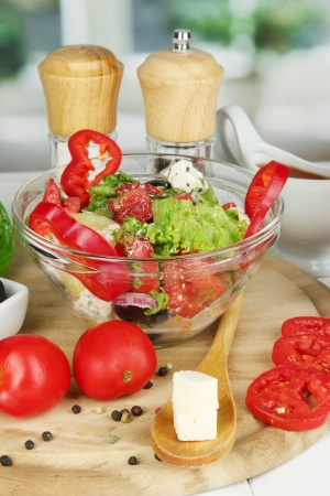 Fresh greek salad in glass bowl surrounded by ingredients for cooking on wooden table on window background Stock Photo - 16413684