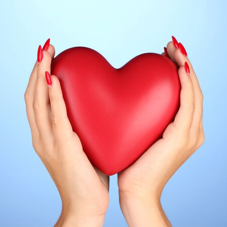Red heart in woman's hands on color background photo