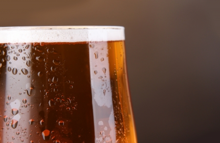 Glass of beer on grey background close-up photo