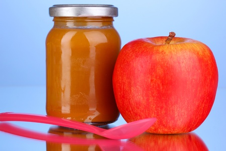 Useful and tasty baby food with apple and spoon on blue background Stock Photo - 16413206