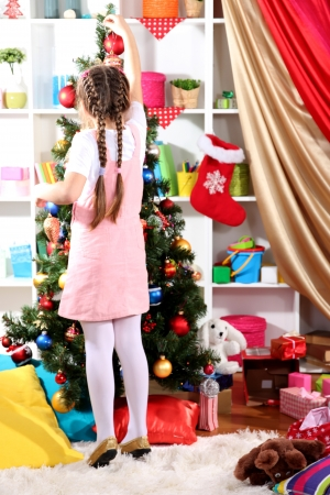 festively: Little girl decorates  Christmas tree in festively decorated room