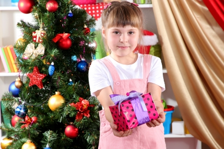 Little girl with Christmas toys in festively decorated room photo