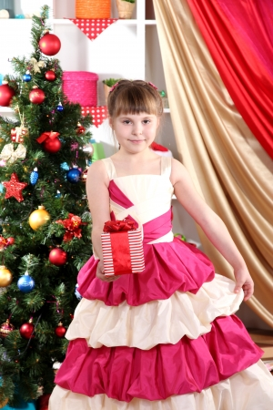 festively: Beautiful little girl in holiday dress with gift in their hands in festively decorated room