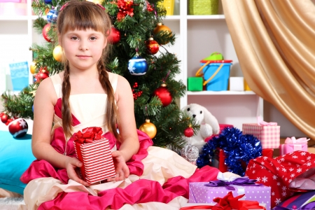 Beautiful little girl in holiday dress with gift in their hands in festively decorated room photo