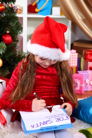 Beautiful little girl in red dress writes letter to Santa Claus in festively decorated room photo