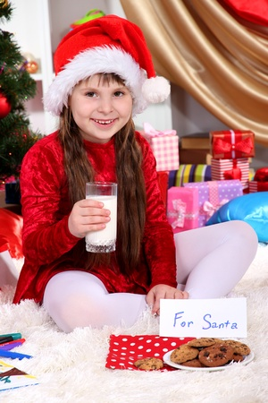 Beautiful little girl with milk and cookies for Santa Claus in festively decorated room photo