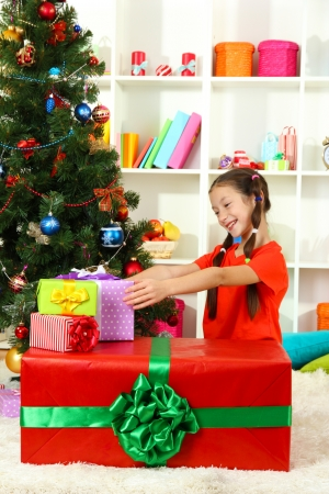 Little girl with large gift box near christmas tree Stock Photo - 17129780