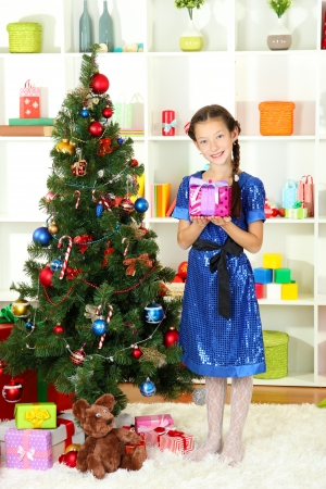 Little girl holding gift box near christmas tree Stock Photo - 17129798