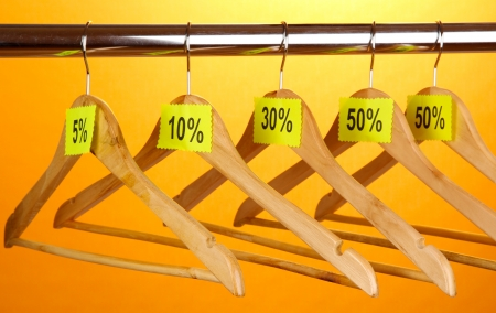 wooden clothes hangers as sale symbol on orange background  photo