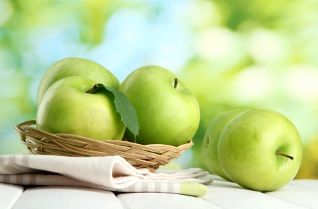 Ripe green apples with leaves in basket, on wooden table, on green background Stock Photo - 16491783