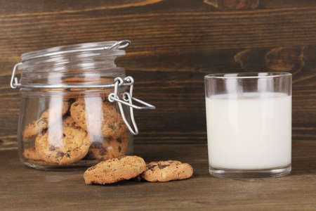 microelements: Glass of milk with cookies on wooden table close-up