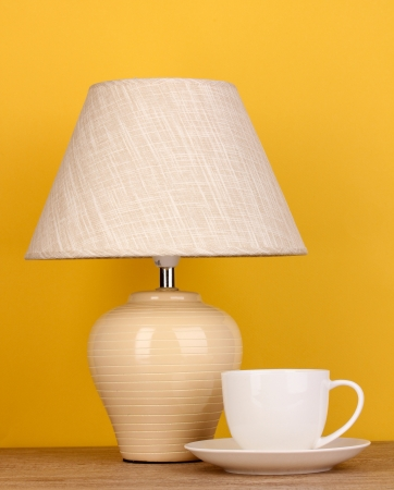 table lamp and cup on yellow background Stock Photo - 16492277