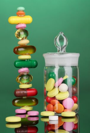 Capsules and pills hill and in receptacle on green background photo