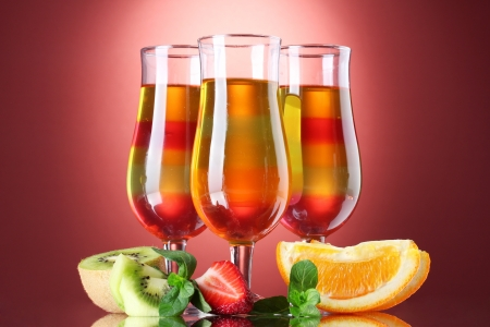 fruit jelly in glasses and fruits on red background photo