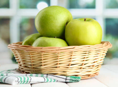 Ripe green apples with leaves in basket, on wooden table, on window background Stock Photo - 16495572