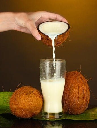 woman's hand pouring coconut milk into a glass on brown background Stock Photo - 16495706