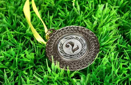Silver medal on grass background photo