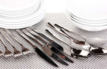 forks, knifes and spoons on red mat close-up Stock Photo