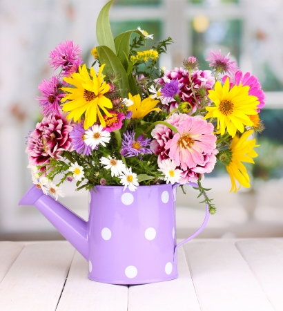 beautiful bouquet of bright flowers in watering can on wooden table photo