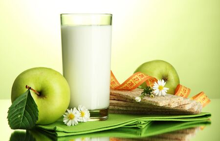 Glass of kefir, apples, crispbreads and measuring tape, on green background Stock Photo - 16495499