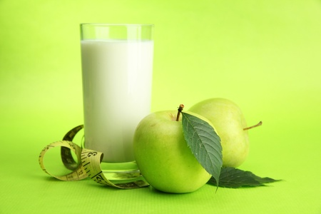 Glass of kefir, apples and measuring tape, on green background Stock Photo - 16495512
