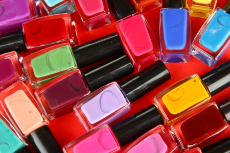 Group of bright nail polishes, on red background photo