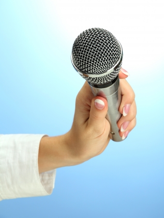 female hand with microphone, on blue background photo
