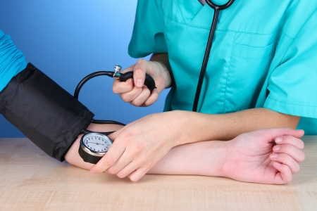 Blood pressure measuring on blue background Stock Photo - 16479658